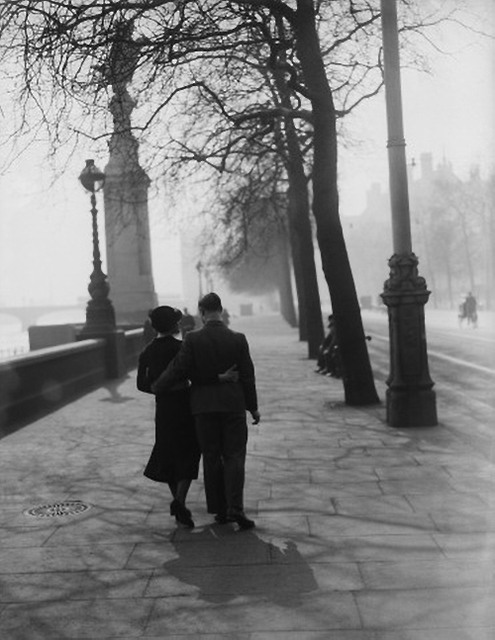 2. a loving couple stroll along the embankment, london, in the sunshine on the first day of spring with their arms round each other, 1935.