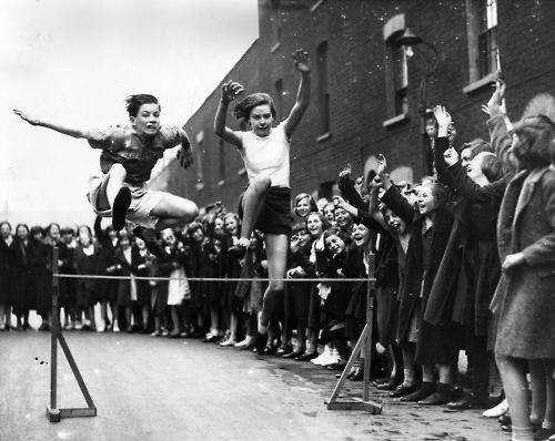 11. 8th May 1936: East London Schools Hurdles champion Grace Adams racing on the Poplar street track in preparation for the annual contest.