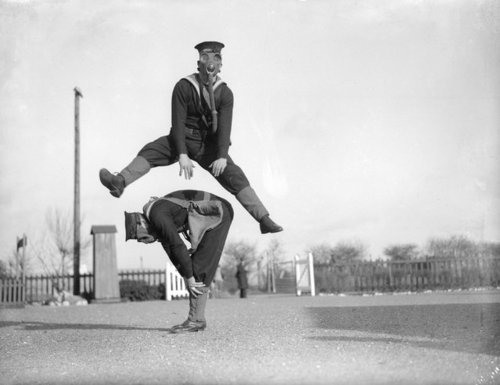13. Able seamen at the Royal Navy Anti-Gas School at Tipnor, Portsmouth play leapfrog wearing gas masks, to accustom them to carrying out strenuous tasks in respirators. 22nd January 1934.