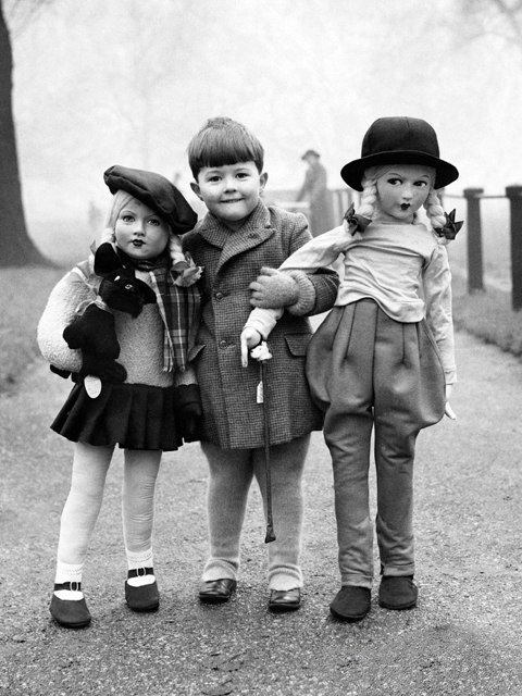 14. A young boy with two life size dolls in Hyde Park, London.