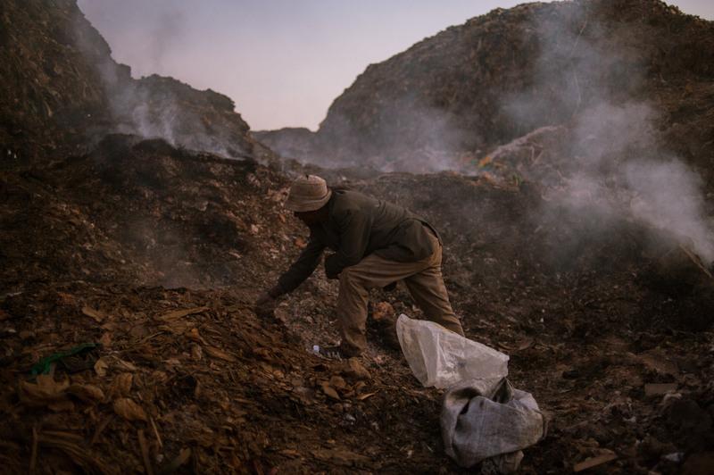 """2.На окраинах свалки работают """"отшельники"""". Они роются уже в перегоревшем мусоре. Здесь намного больше шансов найти метал, ведь за него платят значительно больше чем за бумажные и пластиковые отходы. Но и вред для здоровья значительно выше - они целыми днями дышат пеплом и пылью тлеющих отходов."""
