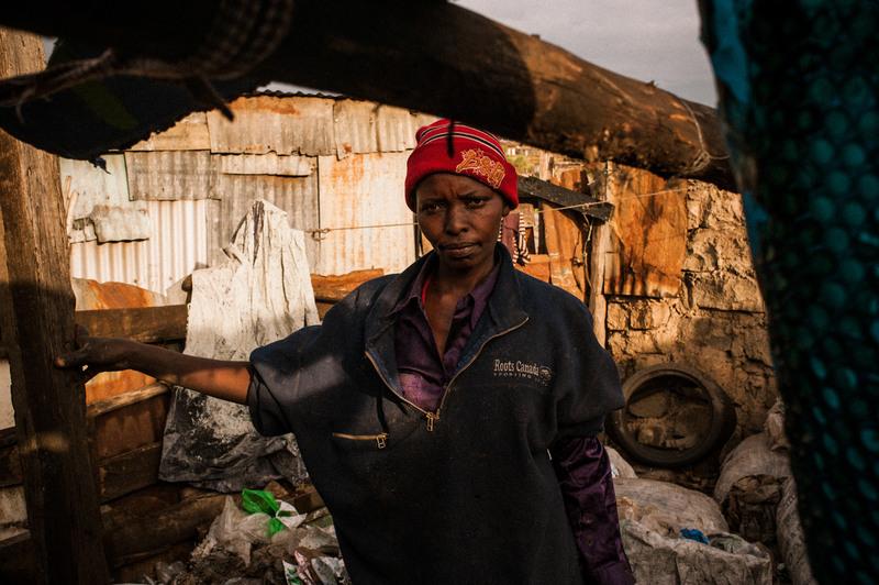 20.На фото Рахаб Ругуру, 42-летняя мать шестерых детей, для них эта свалка – настоящий дом. Она роется в завалах мусора при помощи железной палки, похожей на грабли, для того, чтоб отыскать металлолом, пластмассу, кости, пакеты из под молока, электроприборы. Дневной доход Рабах составляет примерно 2,5 долларов США. Ее дети, в возрасте от 4 до 17 лет активно помогают ей после школы. В 2007 году эта семья переехала в дом (больше похожий на шалаш), находящийся в непосредственной близости со свалкой. Раньше они жили на собственной ферме в в Элдорете на западе Кении, но вспышки насилия и беспорядки в стране, появившиеся после выборов, заставили их поселиться тут.